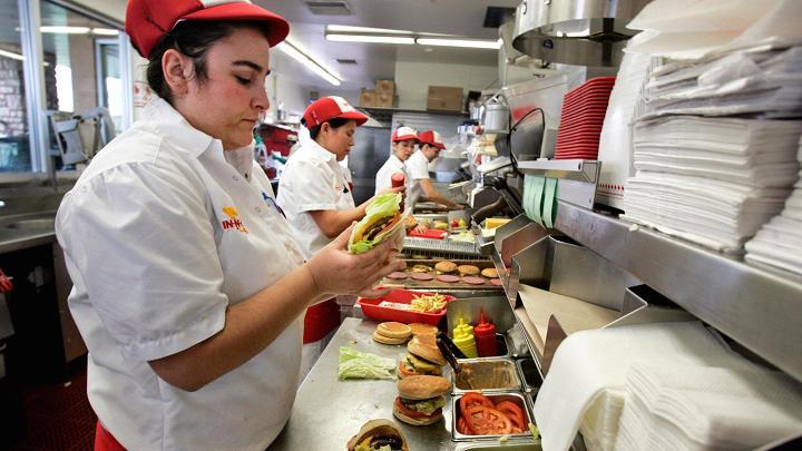 Một nhân viện của In-N-Out Burger đang chuẩn bị Burger bữa trưa cho khách hàng